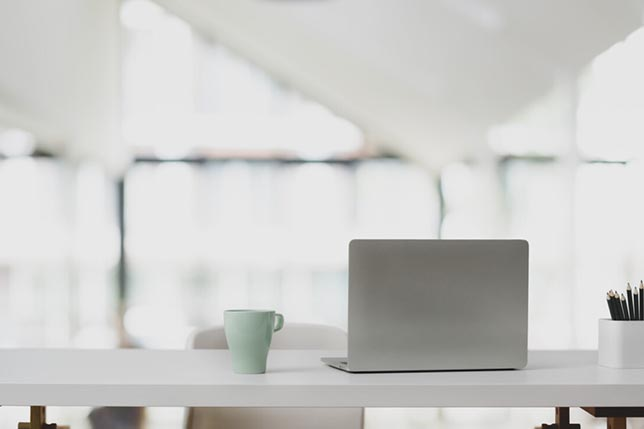 Laptop computer on white table and coffee cup in modern office with blurred background